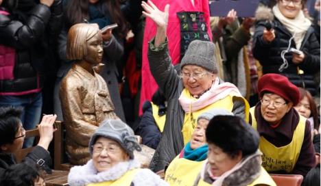 A former South Korean comfort woman reacts with other victims near the statue symbolizing a wartime sex slave during their 1,000th weekly rally to demand an official apology and compensation from the Japanese government in front of the Japanese Embassy in Seoul, Dec. 14, 2011. (AP file photo)