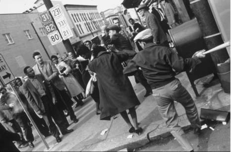 A white man swinging a baseball bat at a black woman the day after the black students were refused service at the courthouse cafeteria