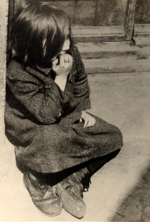 A destitute girl sits on the curb of a street of the Lodz ghetto sm