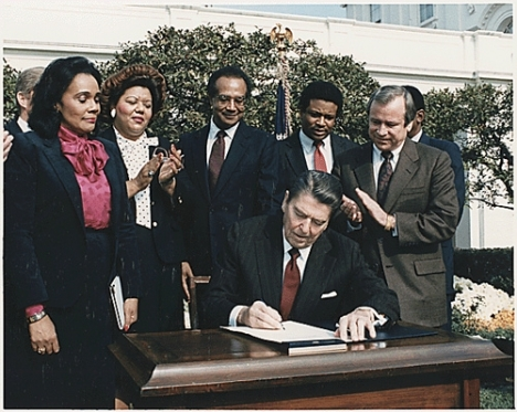 President Ronald Reagan signs legislation to create a federal holiday honoring Martin Luther King, Jr. in the Rose Garden of the White House on November 2, 1983. (by National Archives)