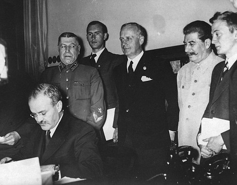 Russian foreign minister Molotov signs Nazi-Soviet Pact in front of his German counterpart Ribbentrop, center, and dictator Stalin in 1939