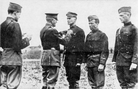General Pershing (second from left) decorates Brigadier General MacArthur (third from left) with the Distinguished Service Cross.