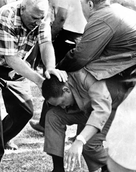 Martin Luther is struck by a stone during a march against housing segregation in Marquette Park on August 5, 1966